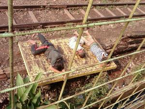 Tampak anak~anak jalanan tidur di atas papan kereta dongkrak disinari hangat mentari pagi.